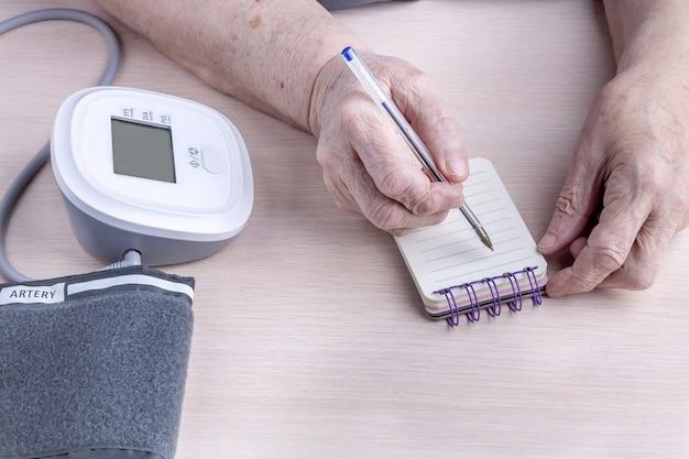 Le mani di una donna anziana annotano le letture di un misuratore di pressione sanguigna in un taccuino