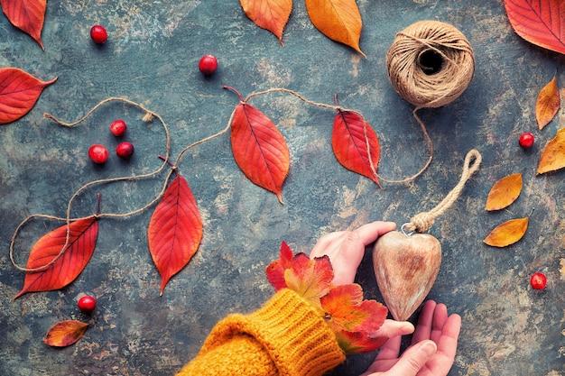 Le mani in maglione arancione tengono il cuore di legno. decorazioni naturali autunnali, rosso vivo, foglie di quercia gialle. lay piatto su sfondo scuro.