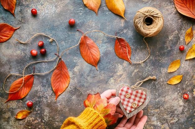 Le mani in maglione arancione tengono il cuore di legno. decorazioni autunnali naturali fatte a mano con foglie di quercia gialle e rosse. lay piatto su legno scuro testurizzato.
