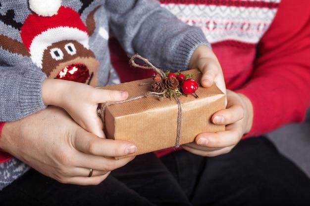 Mani del genitore e del bambino che tengono una confezione regalo di natale.