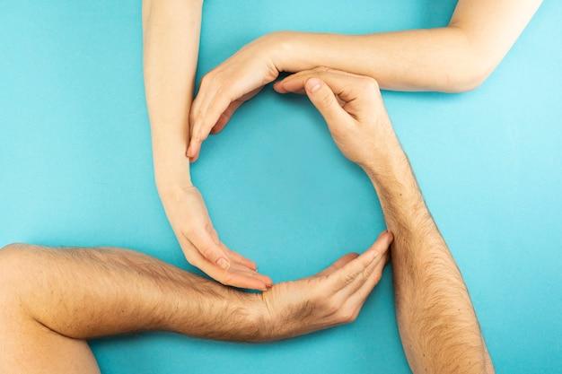 Le mani dei genitori e del bambino sono raccolte in un cerchio con un posto per il testo al centro su uno sfondo blu