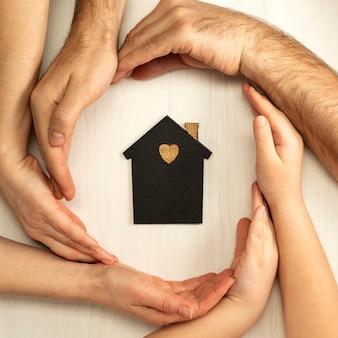 Le mani dei genitori e del bambino circondano il layout di una casa buia su uno sfondo chiaro