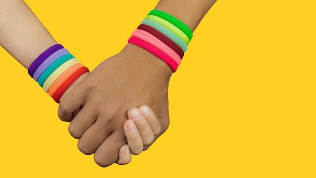Le mani di persone di diverse nazionalità che si tengono l'un l'altra sono il simbolo dell'arcobaleno, il tema lgbt, l'orgoglio, ferma l'odio asiatico, lo spazio della copia