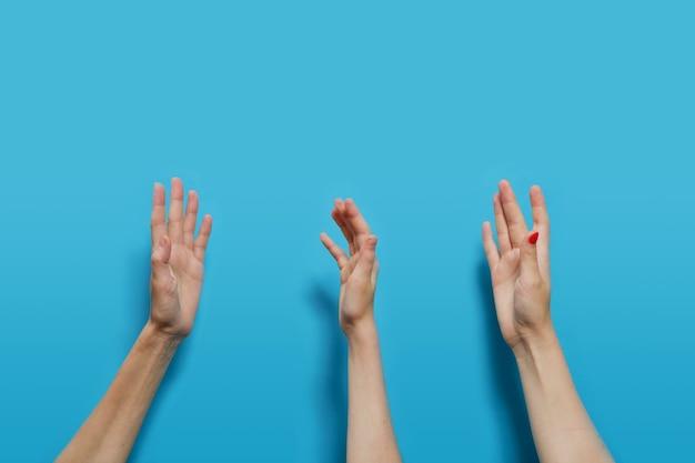 Le mani di persone senza volto di caucasici sono innalzate su uno sfondo blu. Foto Premium