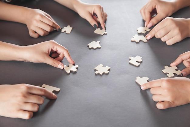Mani di persone che tengono puzzle. partnership, successo, lavoro di squadra