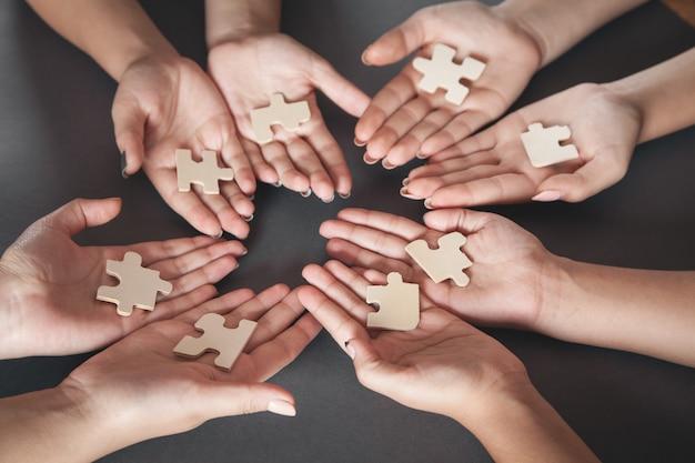 Mani di persone che tengono la partnership di puzzle