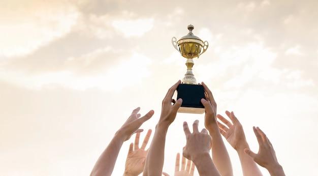 Mani di persone con trofeo d'oro, sport e concetto di concorrenza d'affari.