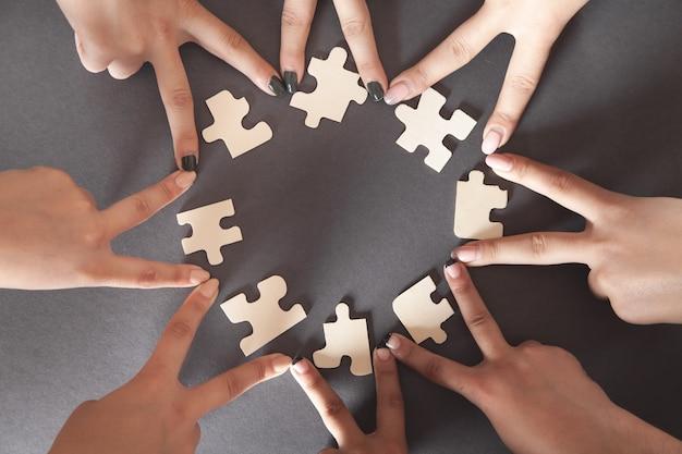 Mani di persone con puzzle