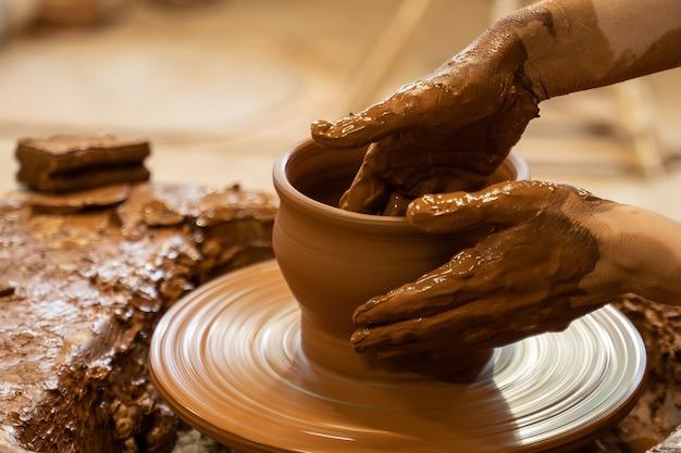 Le mani di un vasaio che creano un vaso di terra sul cerchio donna fanno ceramiche fatte a mano dall'argilla
