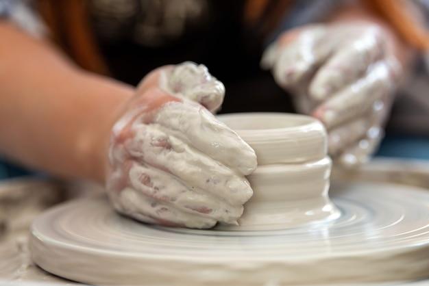 Mani del vasaio. il vasaio fa i piatti di ceramica sul tornio da vasaio