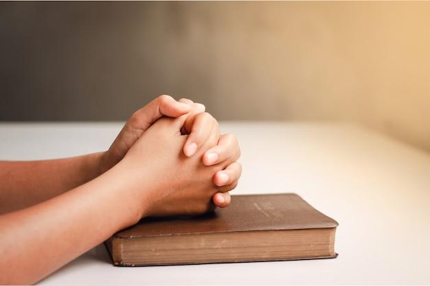 Mani che pregano su una bibbia su un tavolo bianco da vicino