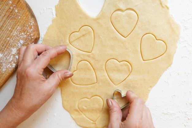 Mani che premono la taglierina del biscotto a forma di cuore nell'impasto