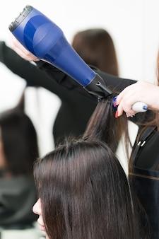 Mani dell'estetista professionista che asciugano i capelli lunghi castani del cliente usando l'asciugacapelli blu e l'ar...