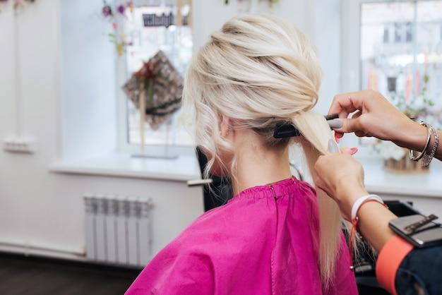 Le mani di un parrucchiere professionista fanno un'acconciatura per una ragazza bionda con i capelli lunghi