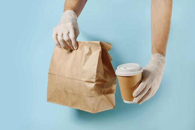 Mani in guanti protettivi che tengono un sacchetto di carta e una tazza di caffè