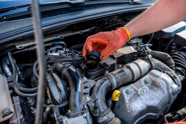 Mani in guanti protettivi con motore dell'auto da vicino. concetto di riparazione auto