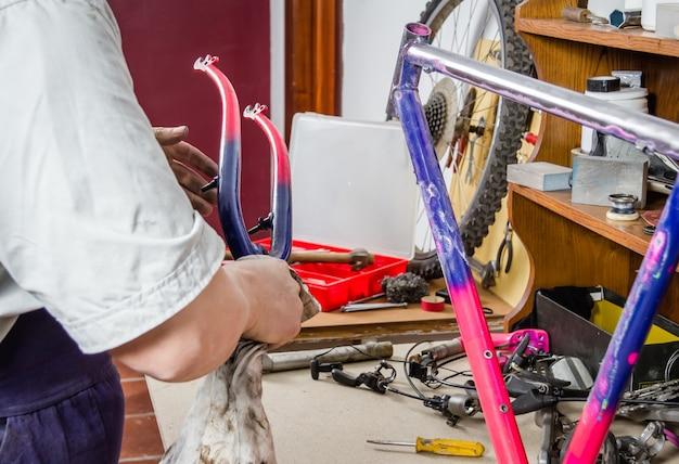 Mani di un vero meccanico di biciclette che puliscono la bici con telaio danneggiato in un'officina