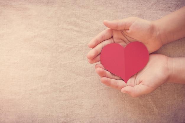 Mani e cuore rosso, assicurazione sanitaria, donazione e concetto di beneficenza, giornata mondiale del cuore