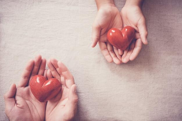 Mani e cuore rosso, assicurazione sanitaria, donazione e concetto di beneficenza