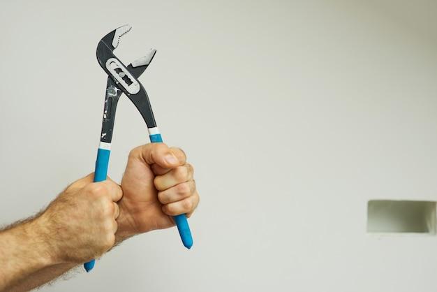 Mani del riparatore che tengono una chiave a tubo con manico blu su sfondo bianco