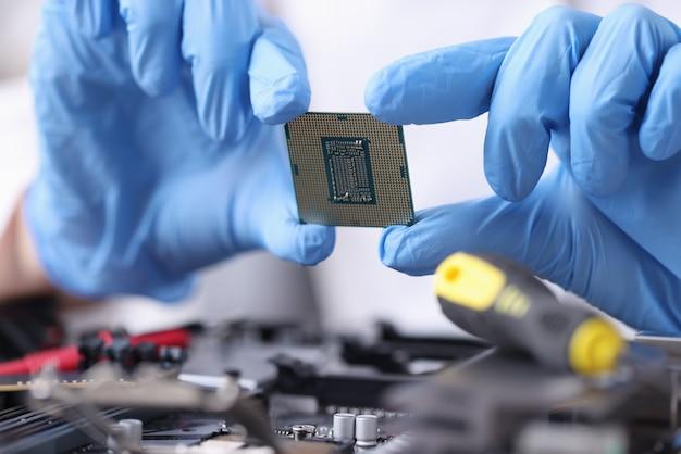 Le mani in guanti di gomma stanno tenendo il primo piano del microprocessore. riparazione e manutenzione di laptop