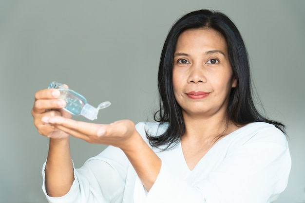 Gel igienizzante mani alcol. uso della donna per lavarsi le mani e proteggere dal corona virus, covid-19.