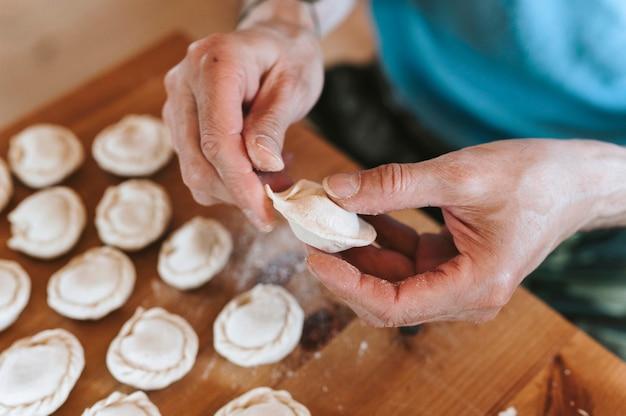 Mani dell'uomo anziano che cucina e modella piccoli gnocchi crudi fatti in casa con carne