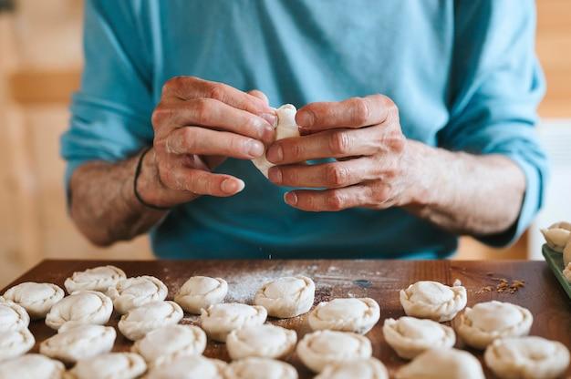 Mani dell'uomo anziano che cucina e modella piccoli gnocchi crudi fatti in casa