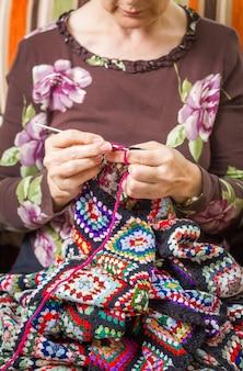 Mani di donna anziana che lavorano a maglia una trapunta di lana vintage con toppe colorate colorful