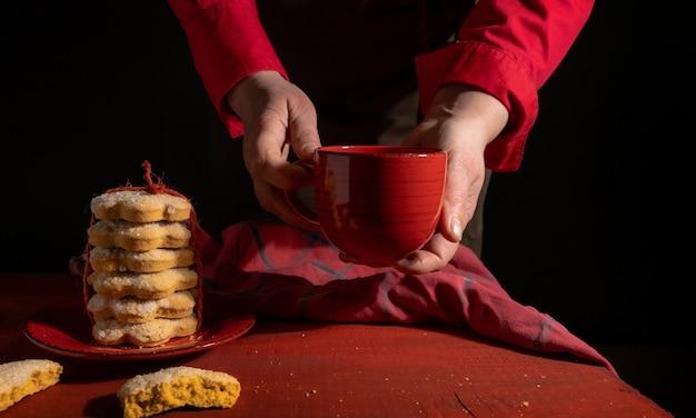 Mani, set di biscotti, tazza di caffè o tè rosso sulla tavola di legno rossa sul nero.