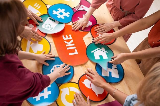 Mani di diversi millennial amichevoli in piedi al tavolo e scegliendo fumetti di carta con icone utilizzate nella comunicazione dei social network