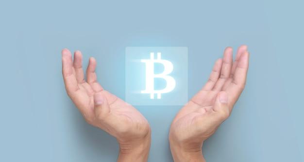 Mani che mostrano l'icona bitcoin come denaro virtuale su digital