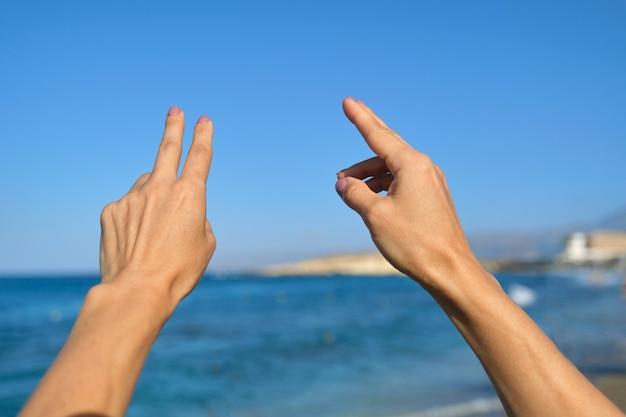 Mani che mostrano il gesto del dito, spazio del mare del cielo blu