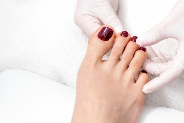 Le mani mostrano le unghie dei piedi di colore rosso