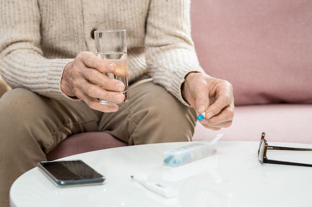 Mani di un uomo anziano malato in abbigliamento casual che tiene pillola e bicchiere d'acqua sul tavolo mentre è seduto sul divano e sta per prendere la medicina