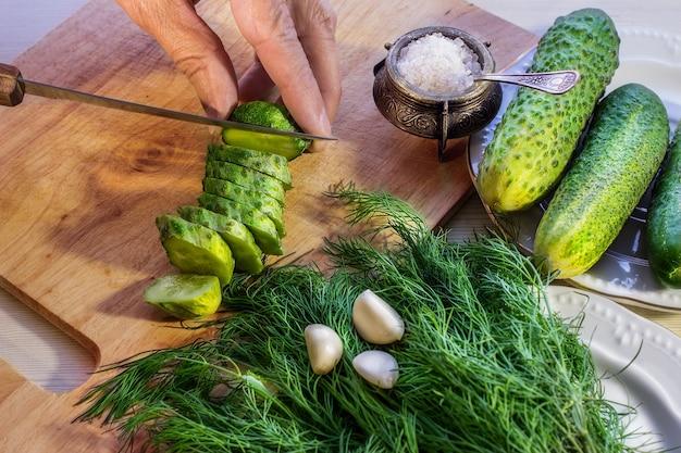 Mani che affettano il cetriolo sul tagliere. cucinare insalata di verdure