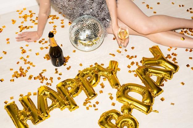 Mani e gambe sottili di giovane donna affascinante con flute di champagne che celebra il compleanno mentre era seduto sul pavimento con coriandoli dorati