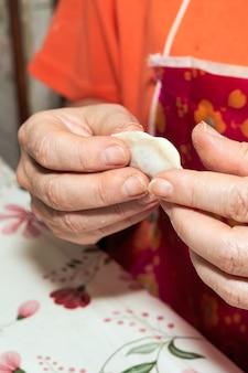 Le mani sporche di farina reggono un gnocco crudo. cucinare gnocchi fatti in casa. colpo verticale