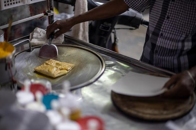 Mani del venditore ambulante che cucinano pane roti dolce in stile tailandese su una padella roti in acciaio o una grande padella piatta. goditi lo street food thailandese.