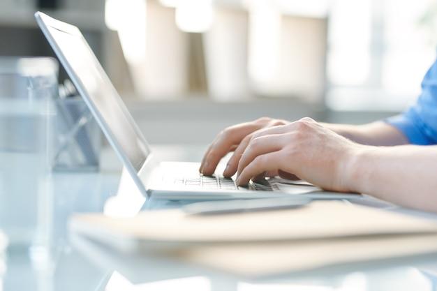 Mani di studente o giovane imprenditore toccando i tasti della tastiera del laptop durante la navigazione in rete al chiuso