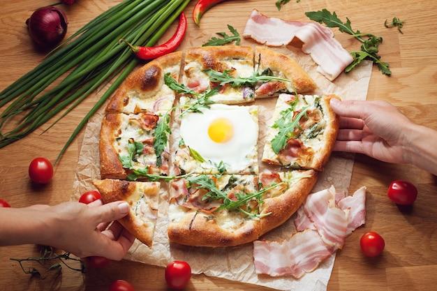 Mani che prendono fette di pizza deliziosa servita sulla tavola di legno