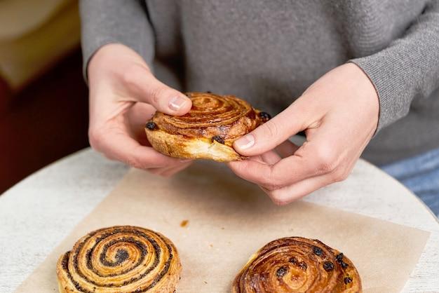 Le mani strappano un pezzo di panino con semi di papavero sullo sfondo del tavolo