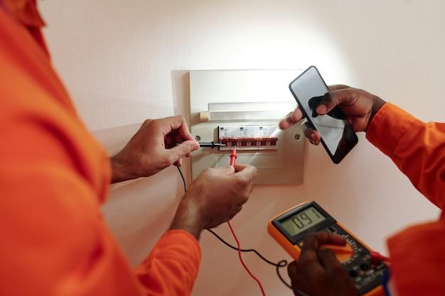Mani dei tecnici che utilizzano il multimetro durante il test della corrente elettrica nel misuratore di wattora