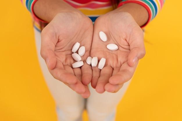 Mani di una ragazza adolescente che presenta additivi alimentari naturali o pillole vitaminiche, farmaci.