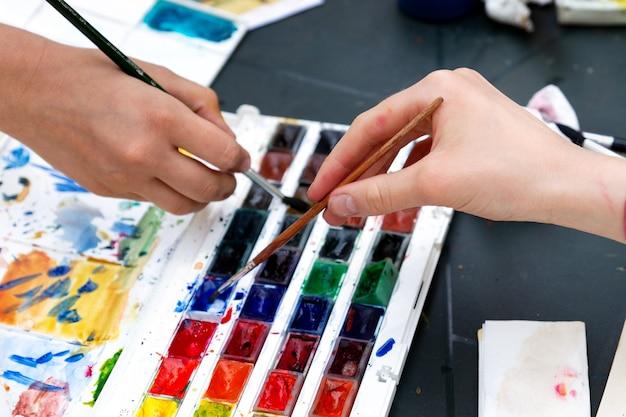 Le mani delle ragazze adolescenti immergono i pennelli nelle pitture ad acquerello in classe d'arte