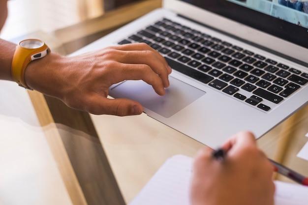 Mani di un adolescente che fanno causa e giocano con il suo laptop - ragazzo che fa i compiti - millennial che guarda video