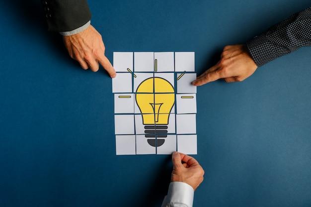 Mani di tre uomini d'affari che assemblano una lampadina disegnata su documenti di post-it