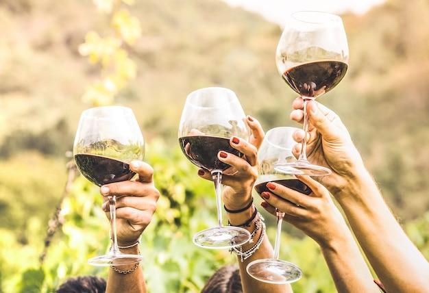 Mani che tostano un bicchiere di vino rosso e amici che si divertono a fare il tifo per l'esperienza di degustazione di vini