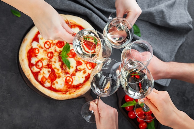 Mani insieme a bicchieri di vino bianco su sfondo pizza
