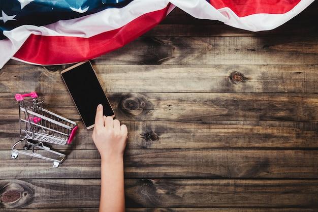 Mani che toccano uno smartphone su uno sfondo di legno con una bandiera degli stati uniti.
